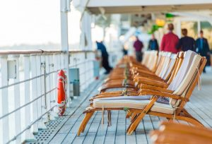 Cruise Ship Wooden Deck Chairs and Some Senior Tourists.