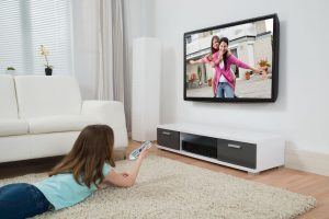 Girl With Remote Control Watching Movie On Television In Living Room